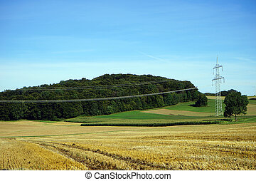 Farm field with pylons and electrical wire in Swabia,...