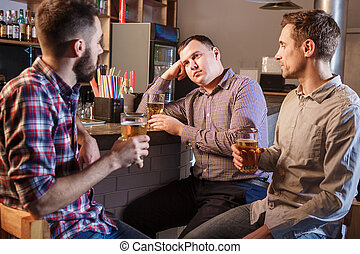 The  friends drinking beer at counter in pub