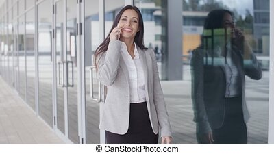 Smiling gorgeous woman on phone outside office - Happy...