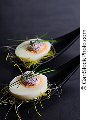 Appetizer on fingerspoon egg with caviaron black background