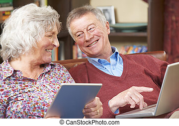 Senior Couple Using Digital Tablet And Laptop At Home
