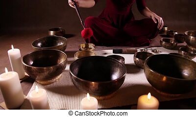 Tibetan bowls dolly shot - Woman playing Tibetan singing...