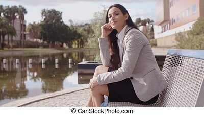 Gorgeous business woman sitting on bench - Gorgeous young...