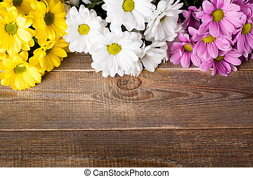Pink, white and yellow oxeye daisy flowers bouquet on wooden...