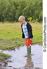 Puddle jumping - A young boy jumping in a muddy puddle...