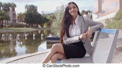 Gorgeous business woman sitting on bench