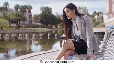 Business woman sitting on bench looking away - Hopeful young...