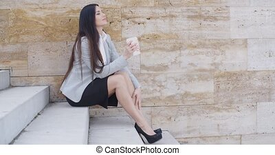 Business woman looking at coffee cup - Cute young business...