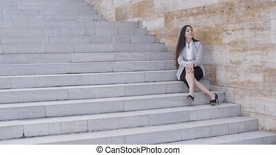 Business woman sitting with crossed legs - Cute young...