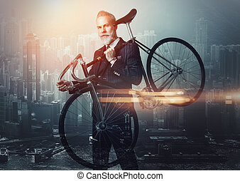 Portrait of stylish gentleman holding a bicycle his shoulder...