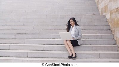 Business woman with laptop on stairs - Cute young business...