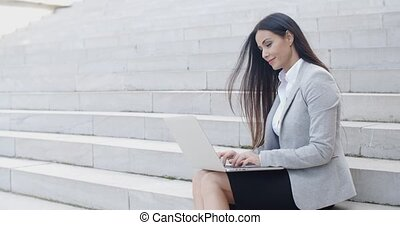 Smiling woman using laptop on stairs - Smiling young...