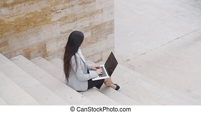 High angle view of woman on laptop on stairs - High angle...