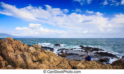Backpack Tourist Sits on Rocky Beach Admires Scenery -...