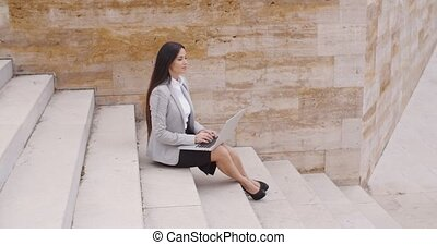Side view of woman using laptop on stairs - Side view of...