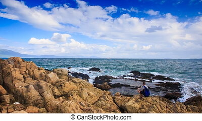 Camera Moves to Backpack Tourist Sitting on Rocky Beach -...