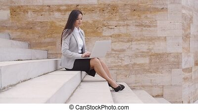 Low angle view of woman using laptop outdoors - Low angle...
