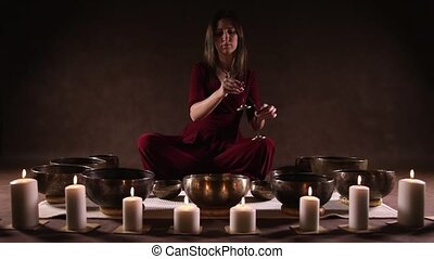 Woman playing tingsha (Tibetan bell - Woman playing Tibetan...