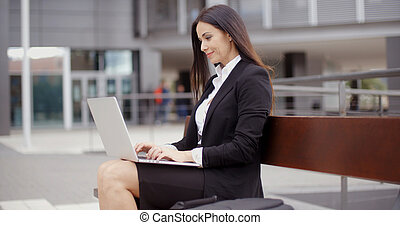 Business woman alone with laptop on bench - Business woman...