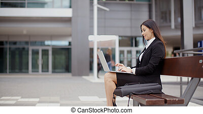 Side view of woman alone with laptop on bench - Side view of...