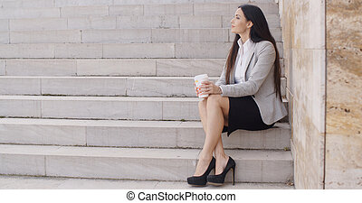 Grinning woman on stairs drinking coffee - Grinning brunette...