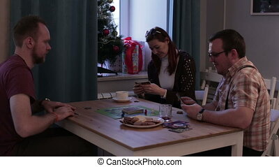 Two men and woman playing a board game with cards -...