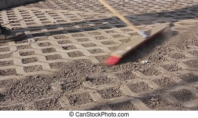 Worker is cleaning - Worker sweeps urban space with a wide...