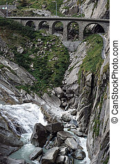 Railway bridge and river near mountain in Switzerland