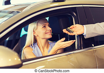 happy woman getting car key in auto show or salon - auto...