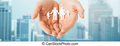 man hands holding paper cutout of family - people, values...