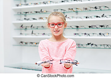 little girl in glasses at optics store - health care,...