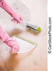 Brush and dustpan - Close-up of sweeping with brush on...
