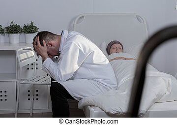 Loosing a patient - Picture of a sad doctor grieving his...