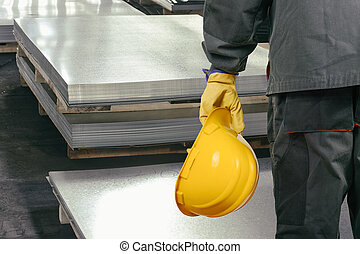 Worker in protective uniform in front of sheet tin metal -...