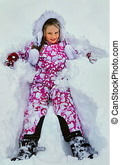 Little girl wearing winter clothes lying in  snow.