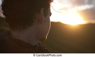 Close up of man staring into the Sunset