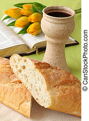 Communion - Chalice with red wine, bread, Holy Bible and...