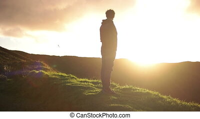 Distant look at man staring into the Sunset - Caucasian man...