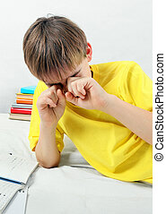 Tired Kid doing Homework - Tired Teenager doing Homework at...