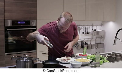 The man in the kitchen preparing fish for frying - The man...