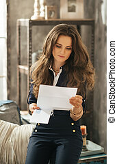 Portrait of stylish young woman with brown hairs reading...