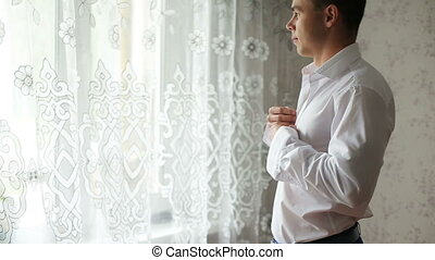 Man buttoning a white shirt - Young bride dress and shirt...