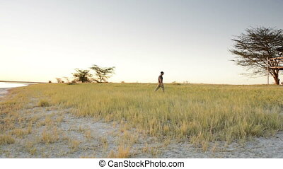Man Walking in Africa at Sunset - Man walks through long...