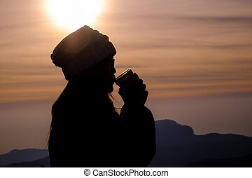 Drinking a warm drink at sunset