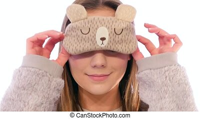 Young Woman with a Cute Sleep Mask Holding it up and Smiling...