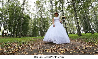 Bride in the wedding dress with bouquet walking in the park