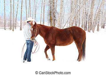 Winter horse - Young cowboy with his horse in a snow forest