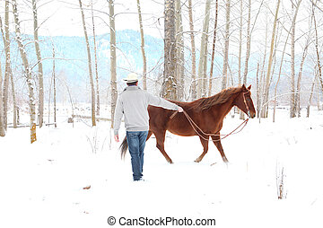 Winter cowboy - Young cowboy with his horse in a snow forest