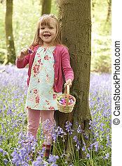 Girl On Easter Egg Hunt In Bluebell Woods