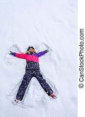 Girl laying on snow and making angel